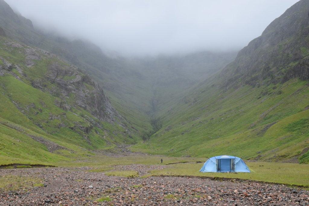 La Lost Valley, a Glen Coe. Panorama tetro e una tenda azzurra in mezzo alla valle.