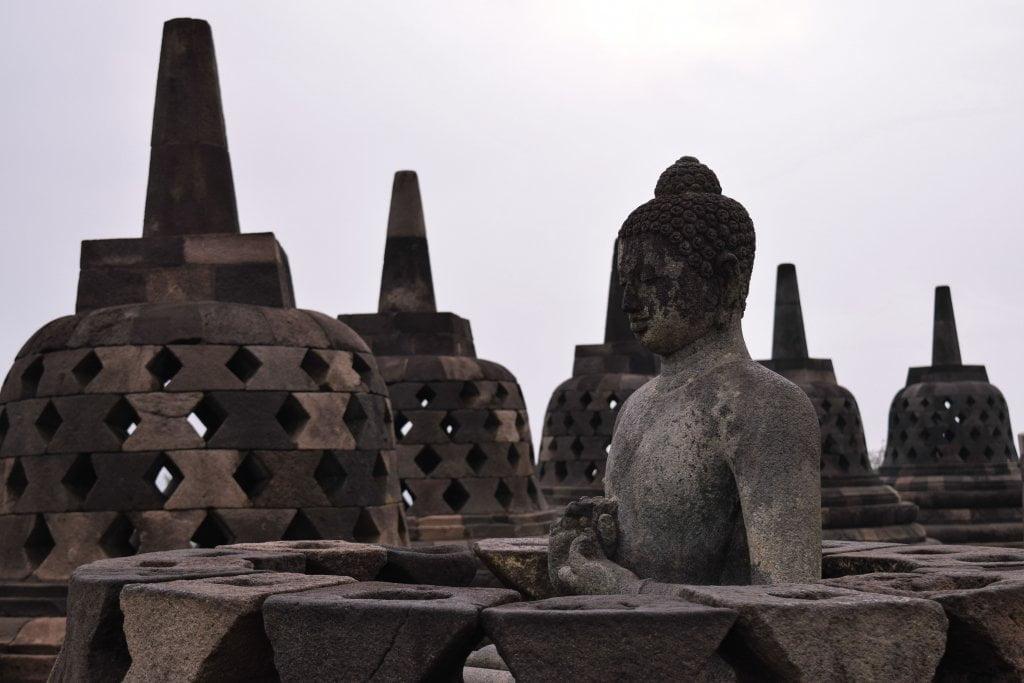 Le campane e una delle tante statue buddiste in cima al tempio Borobudur.