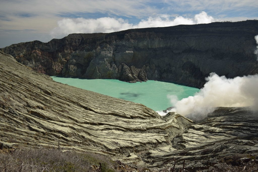 Cosa vedere in Indonesia: la vista del lago azzurro dalla cima del vulcano Ijen. Si vedono i fumi di zolfo.