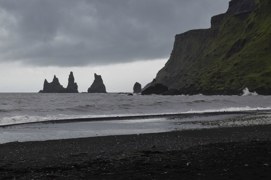 Vik, la spiaggia nera e i faraglioni in mezzo al mare.