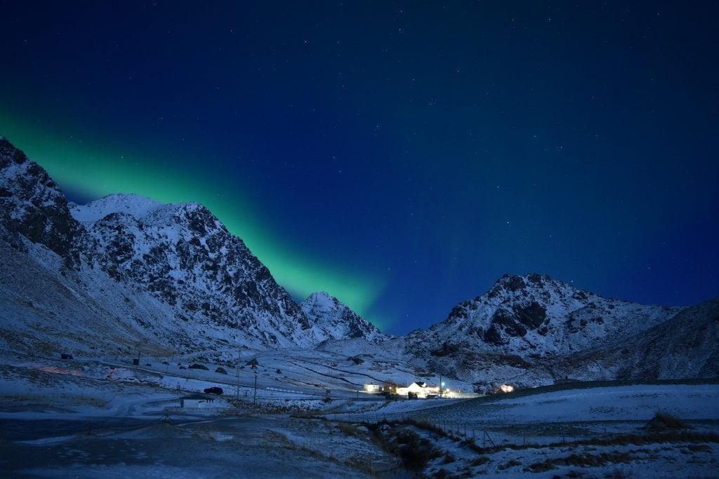 Vedere l'aurora boreale verde nel cielo blu