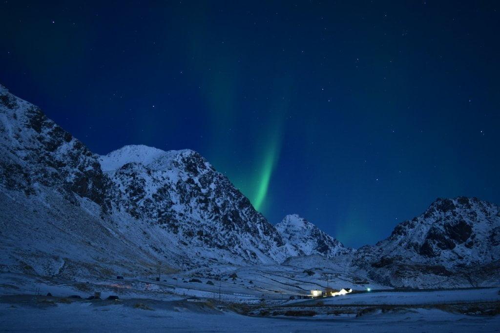 Vedere l'aurora boreale dietro la montagna innevata.