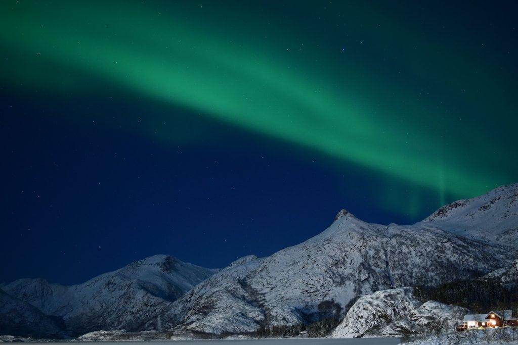 Vedere l'aurora boreale: aurora nel cielo blu alle isole Lofoten
