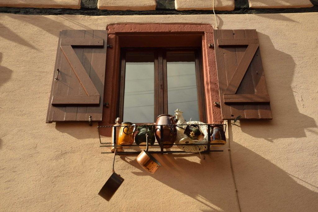 Una finestra di Eguisheim, con pentole appese.